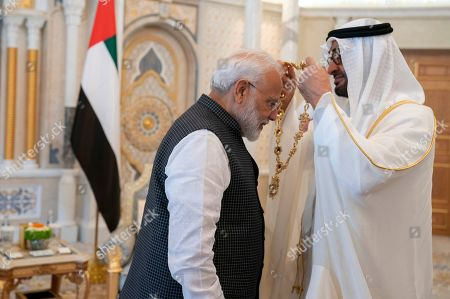 In this photograph made available by the state-run WAM news agency, Indian Prime Minister Narendra Modi, left, receives a medal during his induction to the Order of Zayed from Sheikh Mohammed bin Zayed Al Nahyan, right, in Abu Dhabi, United Arab Emirates, . Modi is on a trip to both the United Arab Emirates and Bahrain, reinforcing ties between India and the Gulf Arab nations as he pursues stripping statehood from the disputed Muslim-majority region of Kashmir