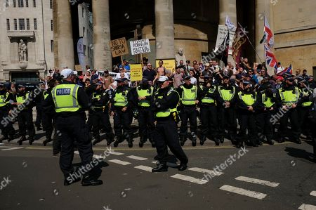 Tommy Robinson supporters hold placards during the rally. Supporters gathered outside BBC to demand the freedom of their jailed right-wing leader Tommy Robinson aka Tommy Robinson. During the rally, police had to intervene and raise their batons when a Police van was attacked by the Tommy Robinson supporters. A person was arrested after the confrontation.