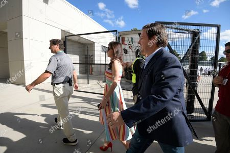 Florida Gov. Ron DeSantis, second from right, and his wife Casey arrive to the stadium before an NCAA college football game between Florida and Miami, in Orlando, Fla