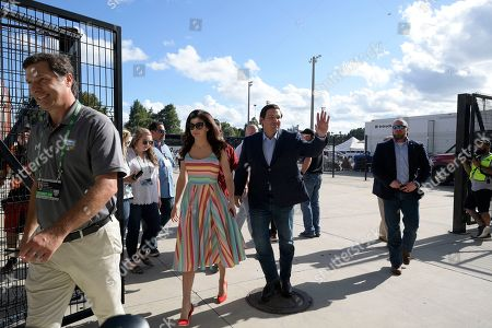 Florida Gov. Ron DeSantis, second from right, waves to Miami fans as he and his wife Casey arrive to the stadium before an NCAA college football game between Florida and Miami, in Orlando, Fla