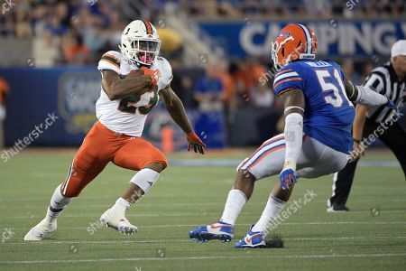 Miami running back Cam'Ron Harris (23) runs in front of Florida linebacker Ventrell Miller (51) after catching a pass during the first half of an NCAA college football game, in Orlando, Fla