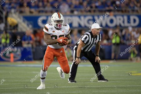 Miami running back Cam'Ron Harris (23) runs after catching a pass during the first half of an NCAA college football game against Florida, in Orlando, Fla