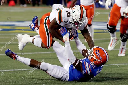 Cam'Ron Harris, Ventrell Miller. Miami running back Cam'Ron Harris (23) knocks Florida linebacker Ventrell Miller, bottom, to the ground as he is tackled during the first half of an NCAA college football game, in Orlando, Fla
