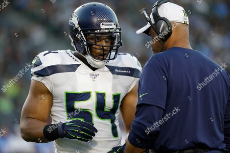 Seattle Seahawks middle linebacker Bobby Wagner (54) talks with Seattle Seahawks defensive coordinator Ken Norton Jr., during the first half of an NFL preseason football game against the Los Angeles Chargers in Carson