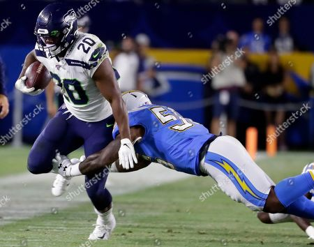 Los Angeles Chargers linebacker Kyle Wilson, right, stops Seattle Seahawks running back Rashaad Penny (20) during the first half of an NFL preseason football game in Carson