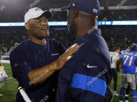 Seattle Seahawks defensive coordinator Ken Norton Jr., left meets up with Los Angeles Chargers head coach Anthony Lynn after an NFL preseason football game in Carson
