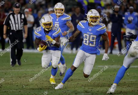 Los Angeles Chargers running back Troymaine Pope (35) follows wide receiver Jason Moore (89) with quarterback Easton Stick (2) watching on a run during the second half of an NFL preseason football game against the Seattle Seahawks in Carson
