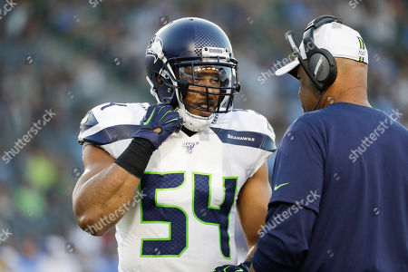 Seattle Seahawks middle linebacker Bobby Wagner talks to Ken Norton Jr. during the first half of an NFL preseason football game against the Los Angeles Chargers, in Carson, Calif