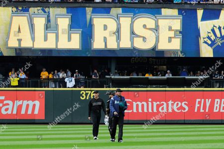 """Seattle Mariners starting pitcher Felix Hernandez walks from the dugout with pitching coach Paul Davis, left, and catcher Omar Narvaez as an """"All Rise"""" King Felix graphic is displayed before a baseball game against the Toronto Blue Jays, in Seattle"""