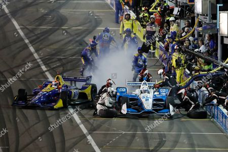 Josef Newgarden (2) pits as Alexander Rossi (27) leaves a trail of smoke as he exits his pit during the IndyCar auto race at World Wide Technology Raceway, in Madison, Ill