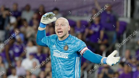 Atlanta United goalkeeper Brad Guzan motions to his teammates during the first half of an MLS soccer match against Orlando City, in Orlando, Fla