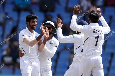 India's Jasprit Bumrah celebrates with KL Rahul after taking the wicket of West Indies' Shai Hope during day four of the first Test cricket match at the Sir Vivian Richards cricket ground in North Sound, Antigua and Barbuda