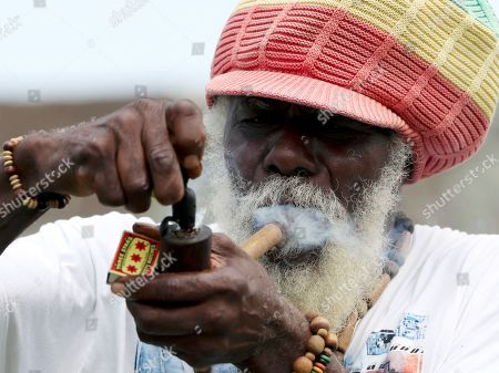 A spectator lights his pipe during day four of the first Test cricket match between India and West Indies at the Sir Vivian Richards cricket ground in North Sound, Antigua and Barbuda