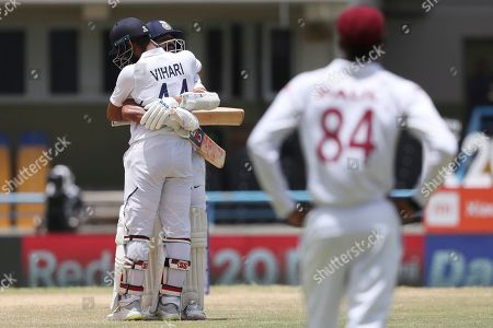 India's Hanuma Vihari congratulates teammate India's Ajinkya Rahane after he scored a century against West Indies during day four of the first Test cricket match at the Sir Vivian Richards cricket ground in North Sound, Antigua and Barbuda