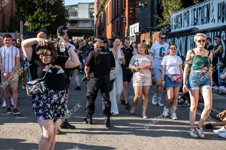 Armed police patrol the venue as fans of Ariana Grande and other musical acts gather at Mayfield Depot ahead of performances.