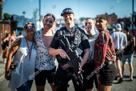 An armed police officer on patrol at the venue poses with fans of Ariana Grande and other musical acts, as they gather at Mayfield Depot ahead of performances.