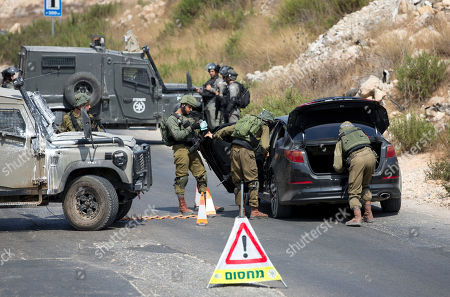 Israeli forces search of Palestinian vehicle near the area of an attack, west of the West Bank city of Ramallah, Sunday, Aug. 25. 2019. An explosion Friday near a West Bank settlement that Israel said was a Palestinian attack killed a 17-year-old Israeli girl and wounded her brother and father, Israeli authorities said