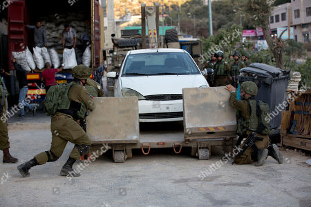 Israeli forces confiscate a car near the area of an attack, west of the West Bank city of Ramallah, Sunday, Aug. 25. 2019. An explosion Friday near a West Bank settlement that Israel said was a Palestinian attack killed a 17-year-old Israeli girl and wounded her brother and father, Israeli authorities said