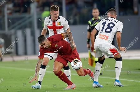 Roma's Aleksandar Kolarov, center, tries to dribble past Genoa's Paolo Ghiglione, right, and Genoa's Lukas Lerager during the Serie A soccer match between Roma and Genoa at the Rome Olympic stadium