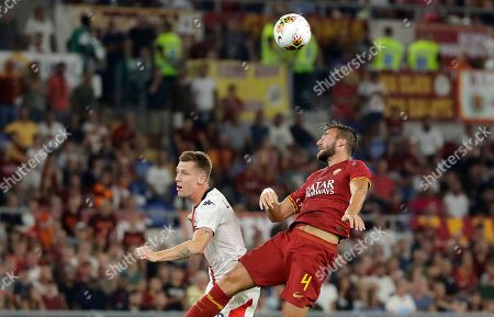 Roma's Bryan Cristante, right, jumps for the ball with Genoa's Lukas Lerager during the Serie A soccer match between Roma and Genoa at the Rome Olympic stadium