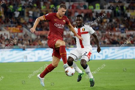 Roma's Edin Dzeko, left, challenges for the ball with Genoa's Cristian Zapata during the Serie A soccer match between Roma and Genoa at the Rome Olympic stadium