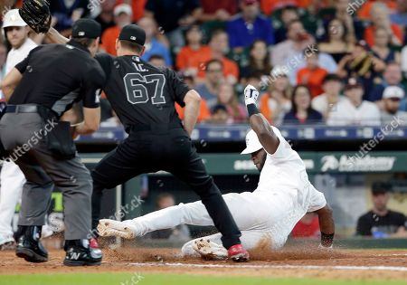 Houston Astros' Yordan Alvarez, right, slides to score from third base on a wild pitch as Los Angeles Angels relief pitcher Taylor Cole (67) waits for the ball at the plate during the eighth inning of a baseball game, in Houston