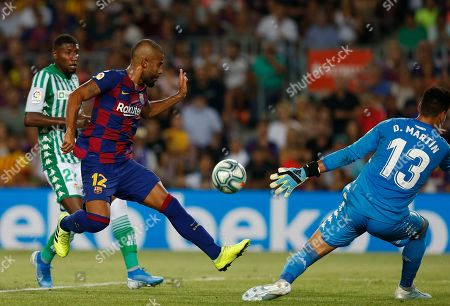 Barcelona's Rafinha, second left, kicks the ball next to Betis' goalkeeper Dani Martin, right, during the Spanish La Liga soccer match between FC Barcelona and Betis at the Camp Nou stadium in Barcelona, Spain