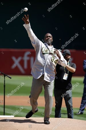 Former Oakland Athletics player Dave Stewart throws out the ceremonial first pitch before a baseball game between the Athletics and the San Francisco Giants in Oakland, Calif
