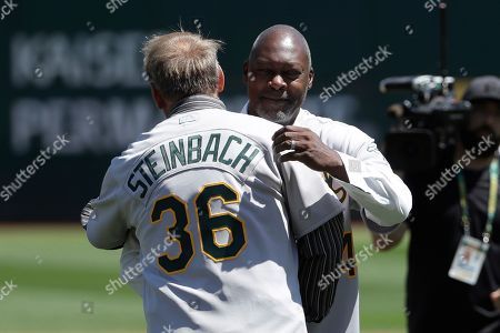 Former Oakland Athletics player Dave Stewart, right, hugs former teammate Terry Steinbach before a baseball game between the Athletics and the San Francisco Giants in Oakland, Calif