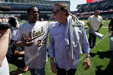 Former Oakland Athletics player Rickey Henderson, left, walks with former manager Tony La Russa before a baseball game between the Athletics and the San Francisco Giants in Oakland, Calif