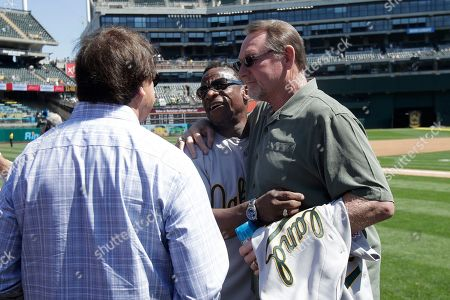 Stock Picture of Former Oakland Athletics player Rickey Henderson, center, hugs former teammate Carney Lansford as former manager Tony La Russa watches before a baseball game between the Athletics and the San Francisco Giants in Oakland, Calif