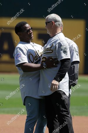 Former Oakland Athletics player Rickey Henderson, left, greets former teammate Curt Young before a baseball game between the Athletics and the San Francisco Giants in Oakland, Calif