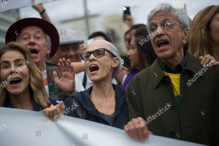 Stock Picture of Brazilian singer Caetano Veloso, right, and Brazilian actress Sonia Braga, center, shout in defense of the Amazon while wildfires burn in that region, in Rio de Janeiro, Brazil, Sunday, Aug, 25, 2019. The country's satellite monitoring agency has recorded more than 41,000 fires in the Amazon region so far this year ? with more than half of those coming this month alone