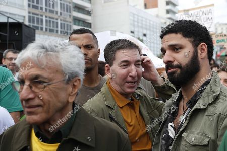 Stock Picture of Brazilian singer Caetano Veloso (L), American journalist Glenn Greenwald (C) and his husband David Miranda (R) take part in a march along with thousands of persons for the conservation of the Amazon rainforest and against the Brazilian President Jair Bolsonaro, at the Ipanema beach in Rio de Janeiro, Brazil, 25 August 2019. Thousands of soldiers have reinforced the firefighting operation in the Amazon, where the number of states that have asked Federal Government aid has increased to seven.