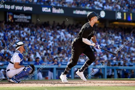 Aaron Judge, Austin Barnes. New York Yankees' Aaron Judge, right, runs to first as he hits a solo home run as Los Angeles Dodgers catcher Austin Barnes watches during the third inning of a baseball game, in Los Angeles