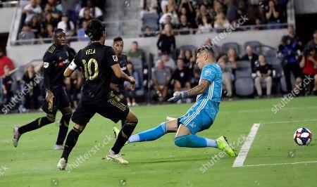 Carlos Vela, David Bingham. Los Angeles FC's Carlos Vela (10) scores past Los Angeles Galaxy goalkeeper David Bingham during the second half of an MLS soccer match, in Los Angeles