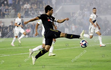 Los Angeles FC's Carlos Vela, center, takes a shot on goal during the second half of an MLS soccer match against the Los Angeles Galaxy, in Los Angeles