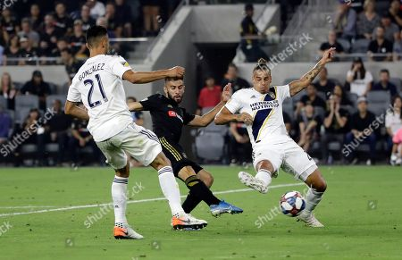 Diego Rossi, Giancarlo Gonzalez, Rolf Feltscher. Los Angeles FC's Diego Rossi, center, shoots between Los Angeles Galaxy's Rolf Feltscher, right, and Giancarlo Gonzalez (21) during the second half of an MLS soccer match, in Los Angeles