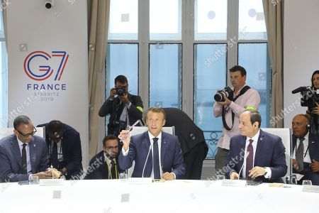 French President Emmanuelle Macron (C), flanked by Rwanda's President Paul Kagame (L) and Egyptian President Fattah al-Sissi (R), shows a watch made of recycled plastic waste from the ocean and working with solar energy, manufactured by French company Awake, during a work session focused on climate in Biarritz, south-west France, 26 August 2019. The G7 Summit runs from 24 to 26 August in Biarritz.
