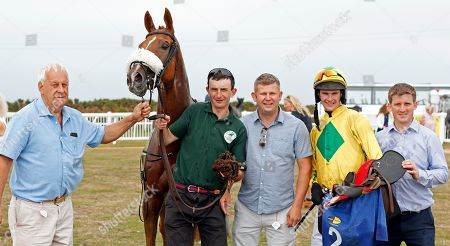 Stock Photo of MAN OF THE SEA (Brendan Powell) with trainer Neil Mulholland (right) and owner Mike Burbidge (left) after The Sue & Nigel Pritchard Sprint Handicap Les Landes Jersey