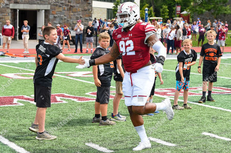 Stock Image of Colgate Raiders defensive tackle Nick Wheeler (92) greets a fan while jogging on the field prior to the game against the Villanova Wildcats on Saturday, Aug., 24, at Andy Kerr Stadium in Hamilton, New York
