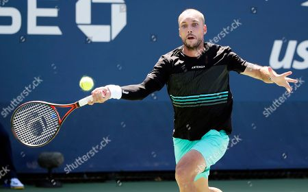 Steve Darcis, of Belgium, returns a shot to Dusan Lajovic, of Serbia, during the first round of the US Open tennis tournament, in New York