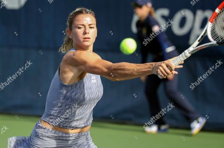 Camila Giorgi, of Italy, returns a shot to Maria Sakkari, of Greece, during the first round of the US Open tennis tournament, in New York