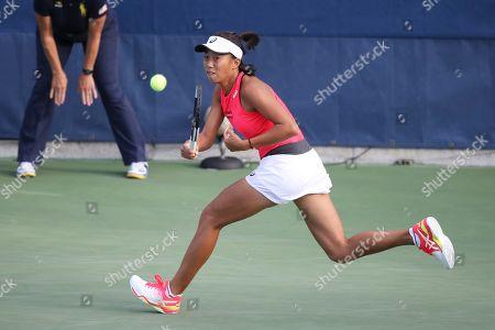 Zhang Shuai, of China, returns a shot to Viktorija Golubic, of Switzerland, during the first round of the US Open tennis tournament, in New York