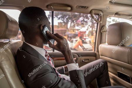 Bobi Wine talks on the phone while driving through Kampala, at the beginning of a day of campaigning.