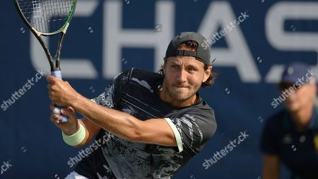Lucas Pouille, of France, returns a shot to Philipp Kohlschreiber, of Germany, during the first round of the US Open tennis tournament, in New York