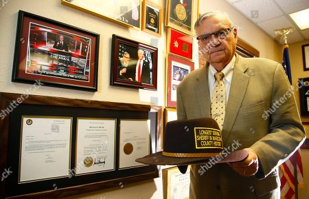 Standing next to his presidential pardon from President Donald Trump, former Arizona Maricopa County Sheriff Joe Arpaio poses for a photograph as he announces his 2020 campaign for Maricopa County Sheriff, trying to get back the job he lost in 2016, in Fountain Hills, Ariz