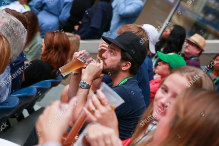 John Magaro enjoys a Heineken while watching