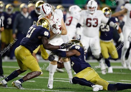 Stock Photo of Asmar Bilal, Jalen Elliott, Trenton Irwin. Stanford wide receiver Trenton Irwin is stopped by Notre Dame safety Jalen Elliott (21) and linebacker Asmar Bilal during the first half of an NCAA college football game in South Bend, Ind. Notre Dame's second-year defensive coordinator Clark Lea has spent all spring, summer and preseason looking for replacements for graduated 2018 tackle leaders Te'von Coney and Drue Tranquill. In grad student Bilal and junior Drew White he may have found two of many