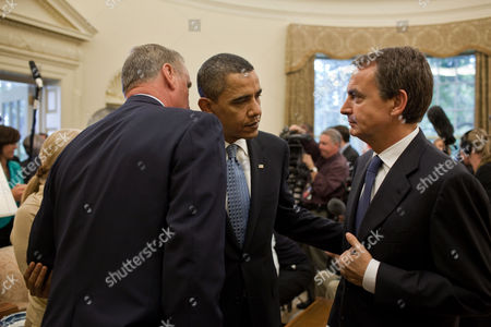 Stock Photo of National Security Advisor General James L. Jones whispers to United States President Barack Obama, as Prime Minister Jose Luis Rodriguez Zapatero of Spain looks on, following their press statements in the Oval Office, Washington, DC, America